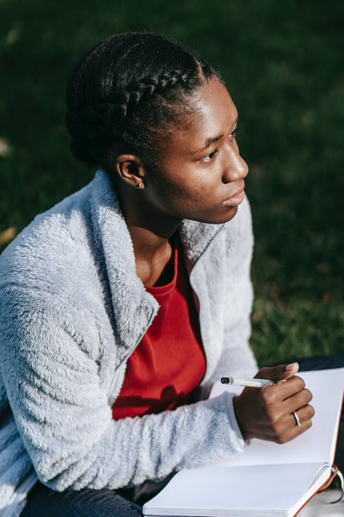 Side view of thoughtful young black lady in casual outfit sitting on grassy lawn while making notes notebook with pen in daytime