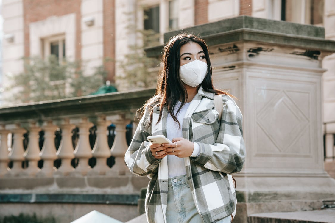 Faceless ethnic female standing in mask in street with cellphone