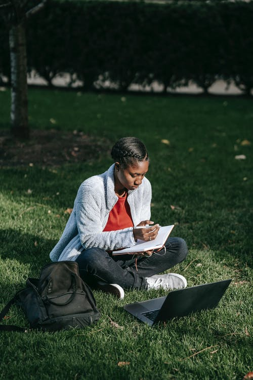 Full body of young black woman in casual outfit with backpack sitting on grass while studying on netbook and making notes in notebook with pen in sunny day