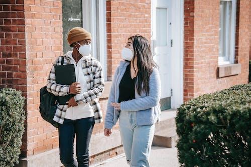 Multiethnic ladies in masks walking in street