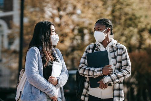 Young multiracial female students in casual outfit and protective masks with documents and laptop walking in university campus