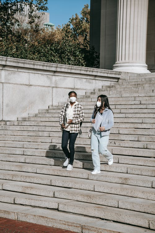 Full body young multiracial female students in protective masks and casual outfits with documents and laptop walking down stairs and talking in campus