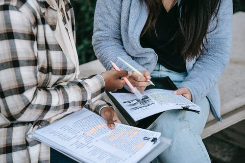 Crop unrecognizable multiracial female students sitting on stone bench in campus and taking notes in papers with printed texts
