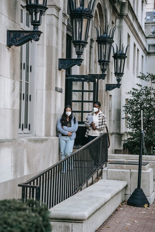 Young multiethnic females in casual wear and face masks carrying folder and going downstairs on outdoor building steps