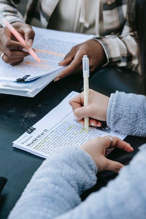 Crop unrecognizable diverse women doing paperwork together
