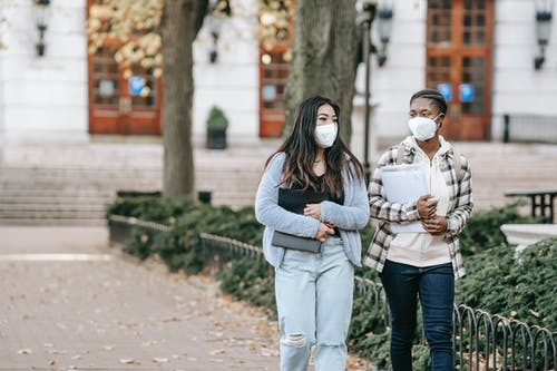 Calm young multiracial female students with folders wearing casual clothes and face masks strolling together on campus sidewalk
