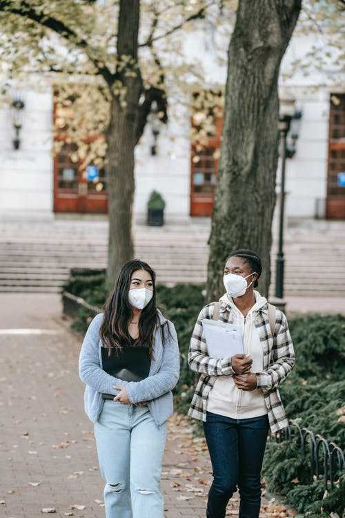 Young multiracial female students in respirators carrying folders and discussing plans while strolling together on campus sidewalk