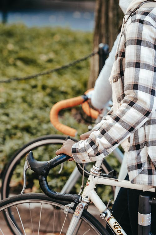 Crop unrecognizable person in checkered shirt riding modern bicycle on city walkway on clear day