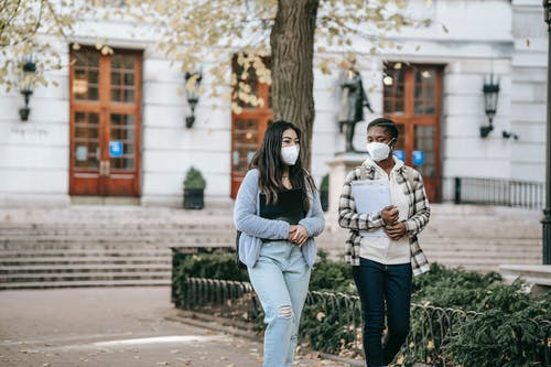 Young diverse women in respirators walking on street and talking