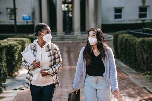 Diverse women in respirators with folders walking on campus sidewalk