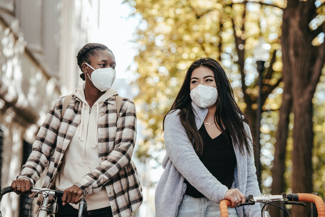 Diverse friends in protective masks with bicycles