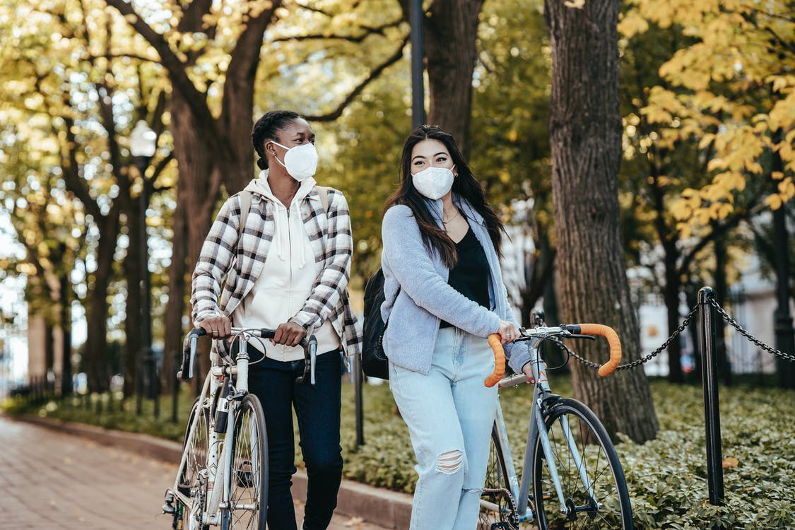 Diverse girlfriends with bicycles walking on pavement in park