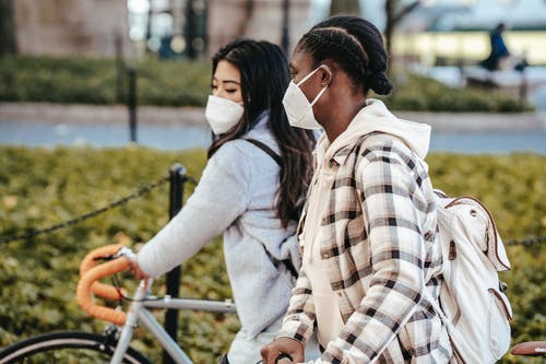 Diverse girlfriends wearing masks walking with bicycles
