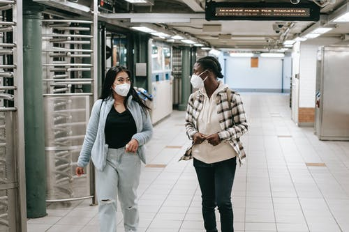 Multiracial women in protective masks walking together in hallway of subway and looking at each other