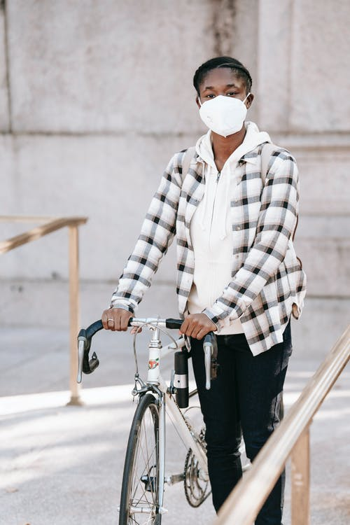 African American female wearing protective mask in casual clothes standing with bicycle near handrail and looking at camera