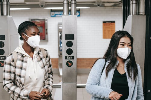 Multiethnic girlfriends in casual wear and protective masks entering metro station during coronavirus epidemic