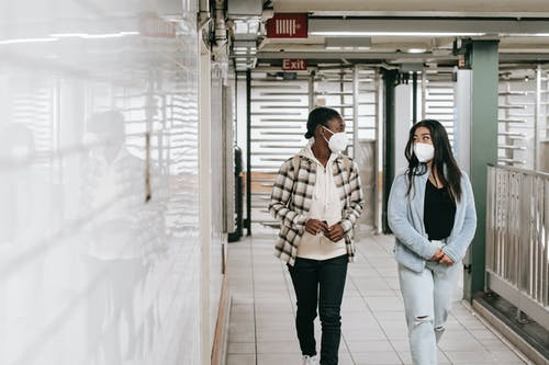 Multiracial women in protective masks walking in passage of underground during coronavirus epidemic and looking at each other