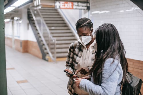 Anonymous multiracial students watching smartphones in subway station