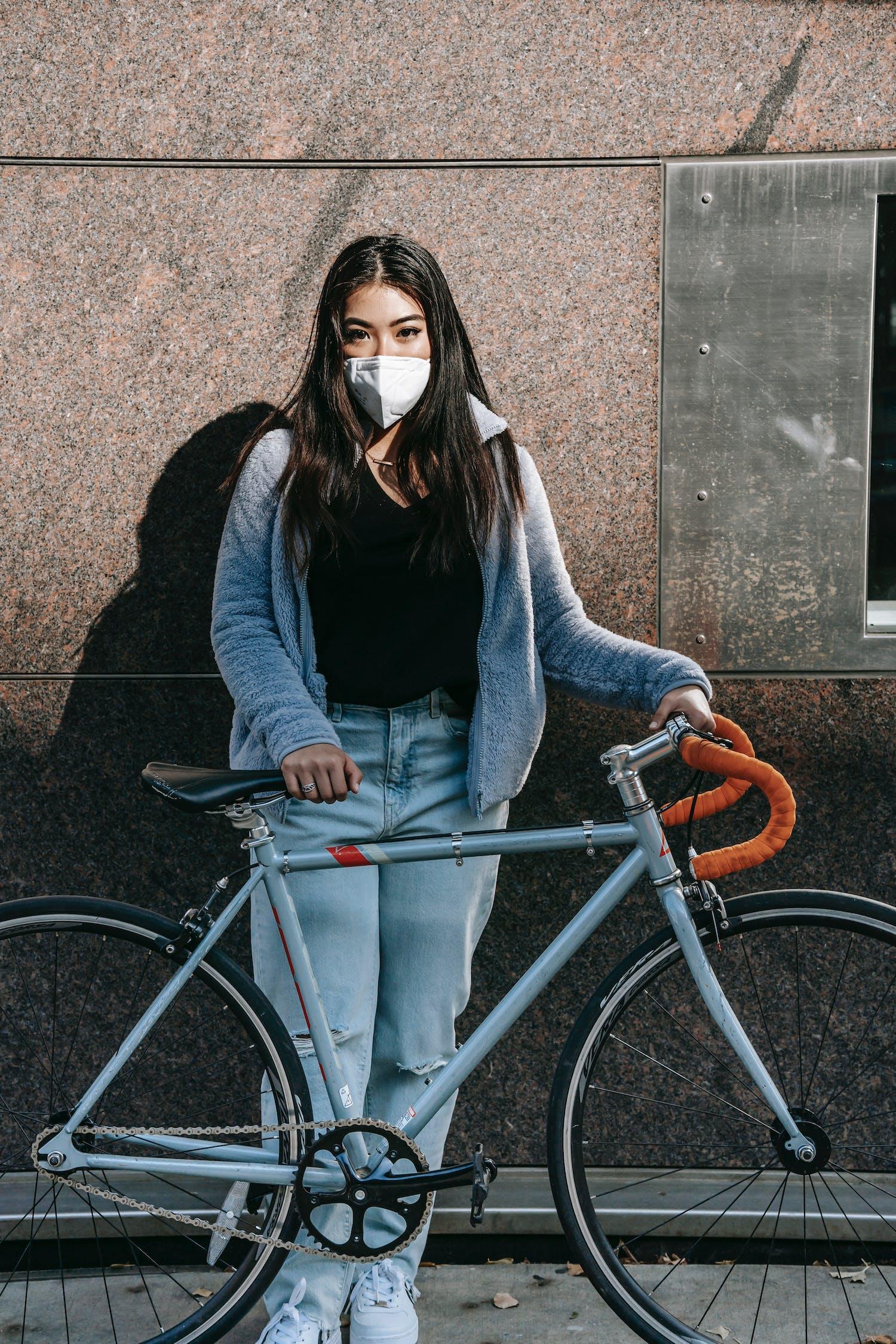 Femme En Chemise à Manches Longues Grise Et Jean Bleu Denim Debout à Côté De Vélo Bleu