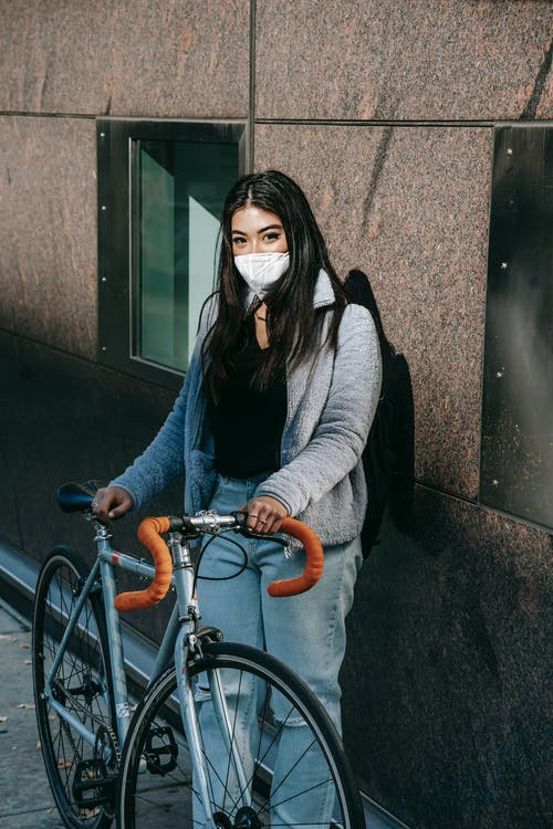 Anonymous young ethnic female in respiratory mask and casual wear with bicycle looking at camera in city