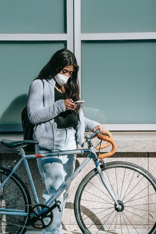 Unrecognizable millennial Asian female in mask with bike text messaging on cellphone near urban building in sunlight