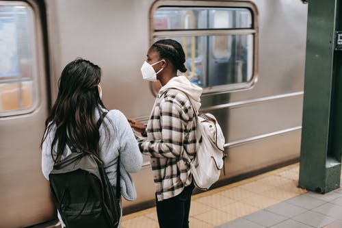 Anonymous diverse female students against metro on platform