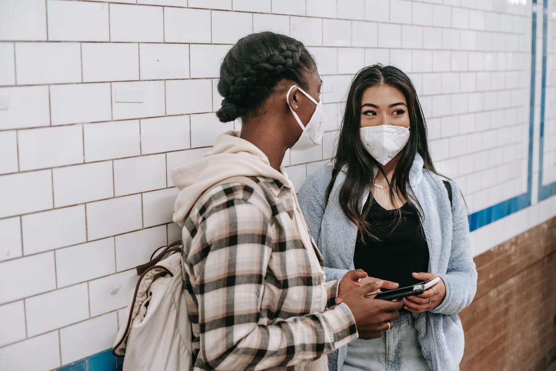 Unrecognizable black woman with rucksack talking to Asian girlfriend in respiratory mask with cellphone near tiled brick wall during coronavirus period