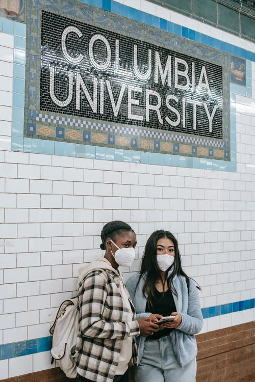 Unrecognizable young multiethnic female friends in masks with cellphones near tiled brick wall with Columbia University inscription in underground