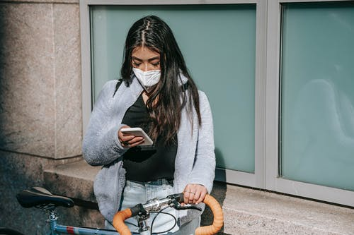 Anonymous young ethnic female in mask browsing internet on cellphone between bicycle and building in town