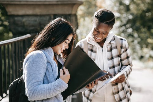 Cheerful multiracial students watching folders while studying on street