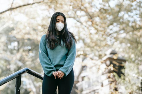Young contemplative ethnic female in casual apparel and respiratory mask looking down with clasped hands in city