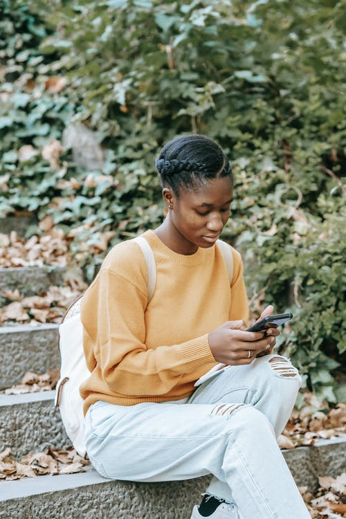 Young focused African American female with backpack surfing internet on mobile phone while resting on city staircase in fall