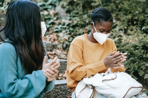 Young multiracial female friends in casual clothes and protective face masks wiping hands and sitting on stone stair in park