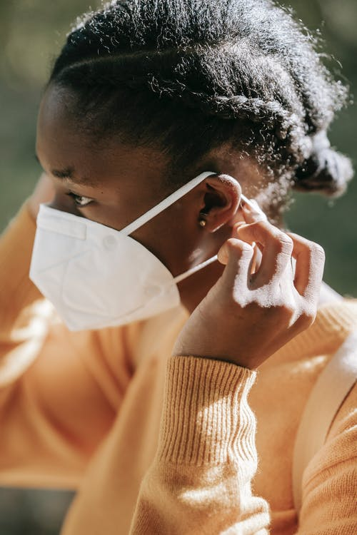 Crop black woman putting on face mask in park