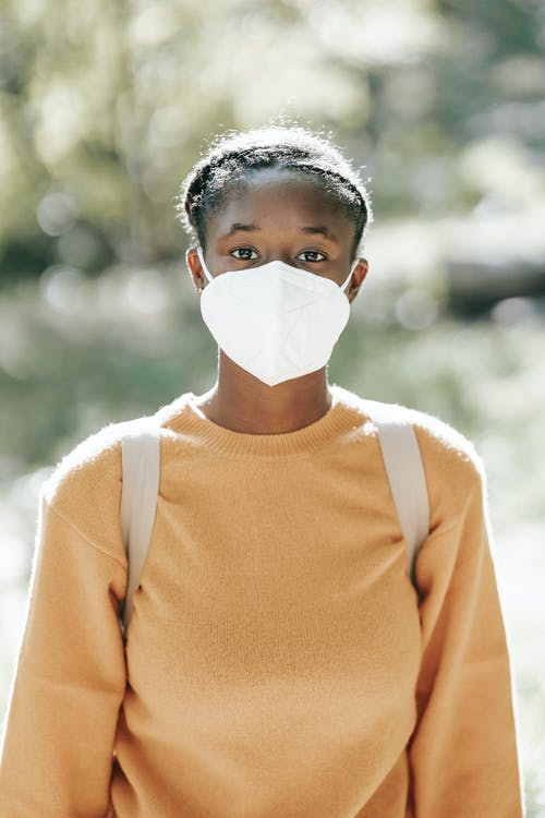 Calm black woman in mask standing in sunny park