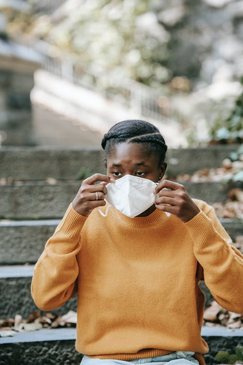 Young black woman putting on protective mask in park