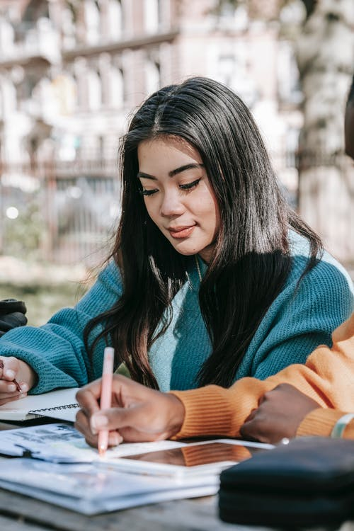 Content young multiracial female students in warm sweaters working on university project together and taking notes in copybooks while sitting at table in park