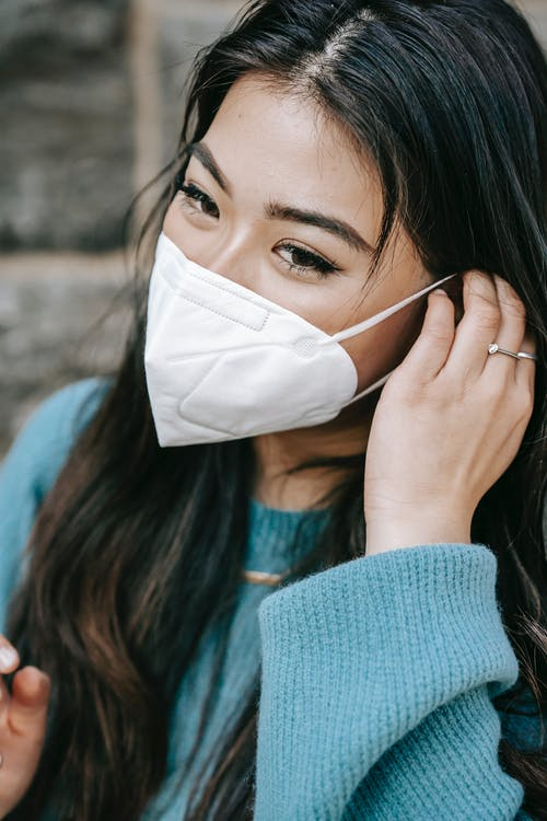 Crop attractive Asian woman putting on mask on street