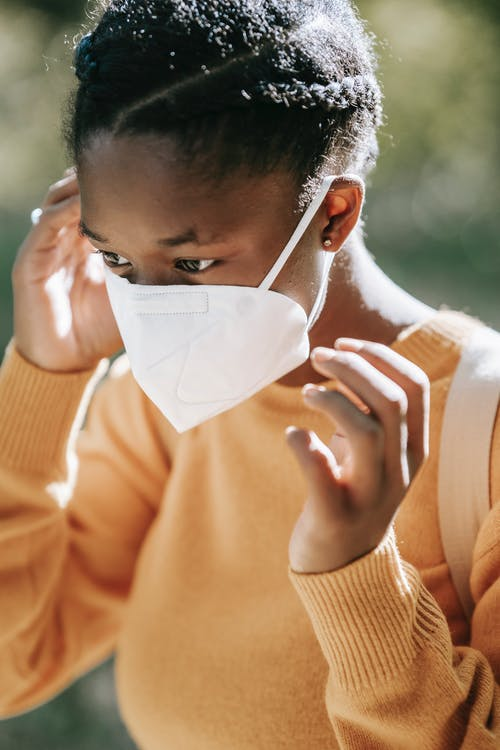 Crop calm young African American female in yellow sweater putting on face mask and looking away while standing on blurred park background on sunny autumn day
