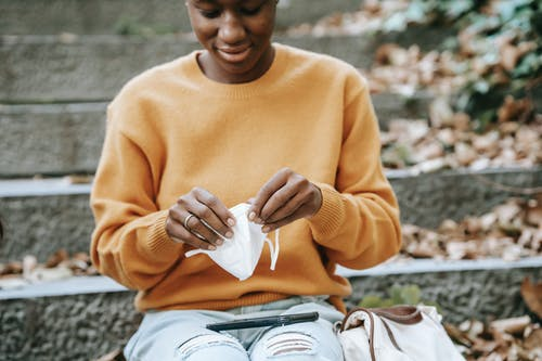 Crop content young African American female wearing jeans and yellow sweater putting on protective face mask and sitting on staircase in autumn sunny park