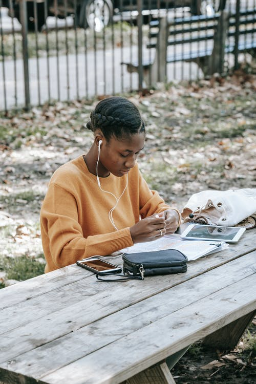 Young concentrated African American female using smartphone and earphones while learning data from copybook at table on street in daytime