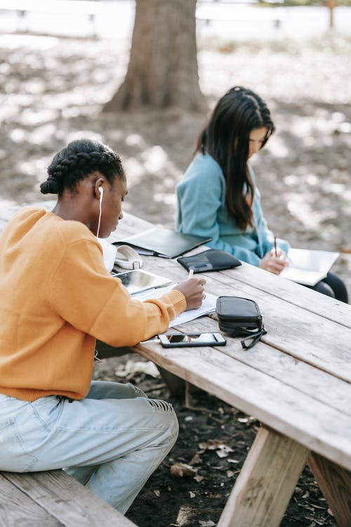Focused anonymous students in casual outfit writing report in notebooks at table in park
