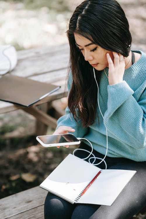Crop ethnic young female with empty copybook checking mobile phone while listening to music in earphones