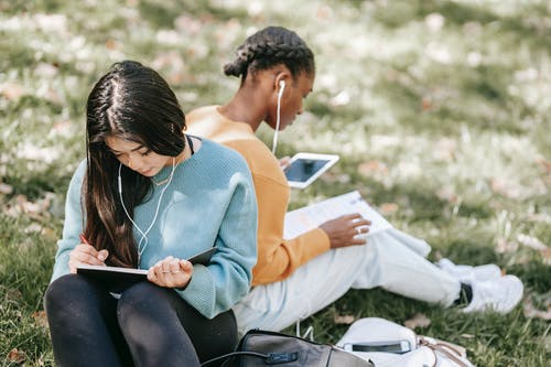 Multiracial young women using tablet and writing in notebook