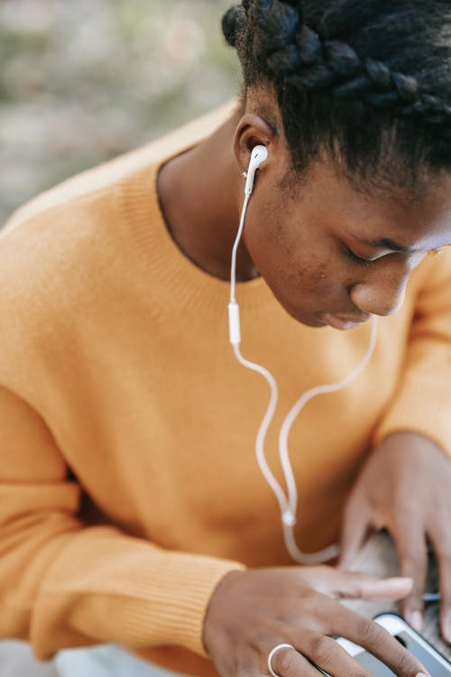 Black woman in earphones scrolling smartphone