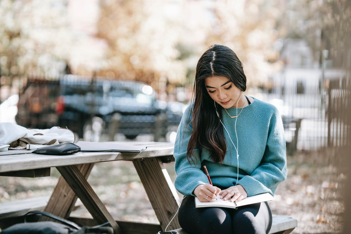 Young focused Asian woman in earphones writing in diary