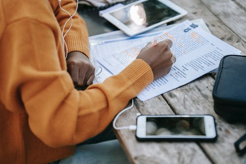 From above of crop anonymous African American female in sweater studying and outlining words on paper at table with smartphone