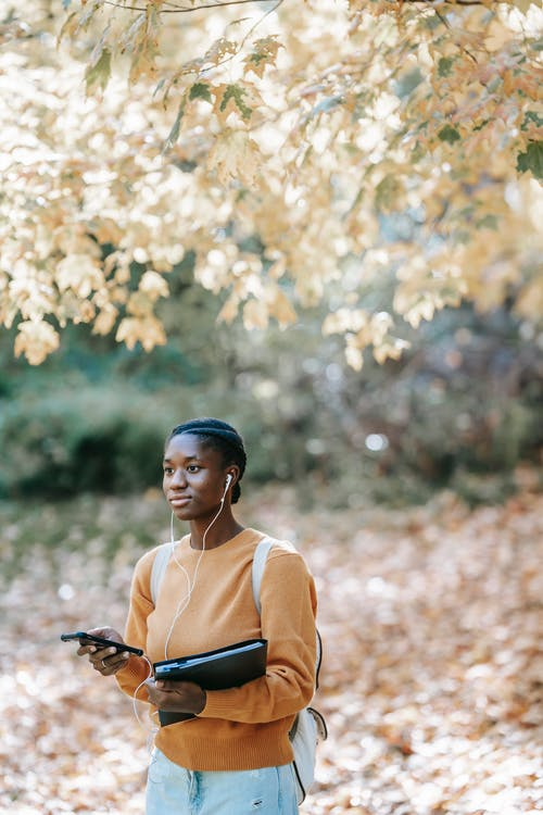Young African American female with folder looking away and using earphones with mobile phone while listening to music near tree