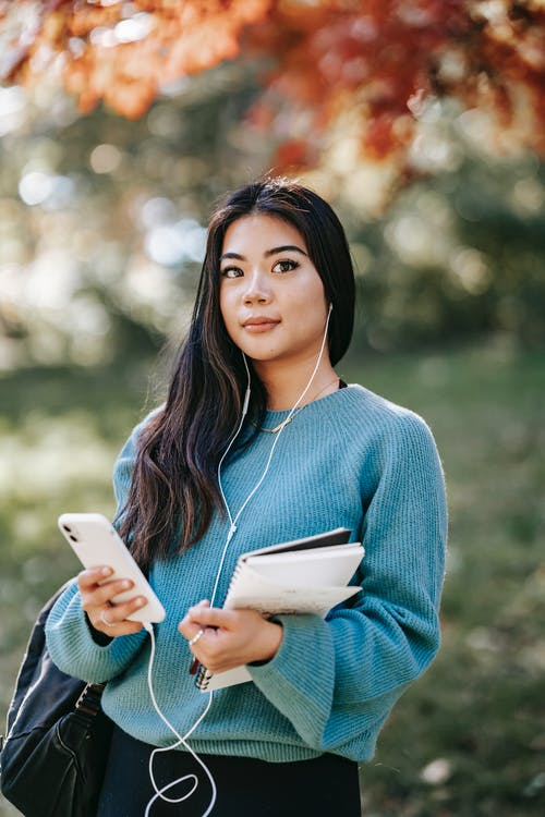 Content young ethnic female in sweater listening podcast with earphones and mobile phone on blurred background of park