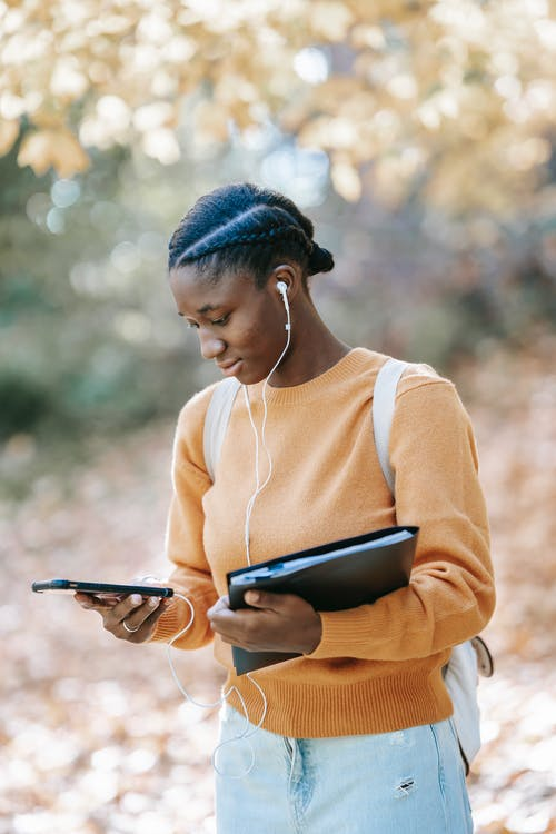 Young African female with folder  in casual outfit in earphones listening to music with mobile phone on blurred background